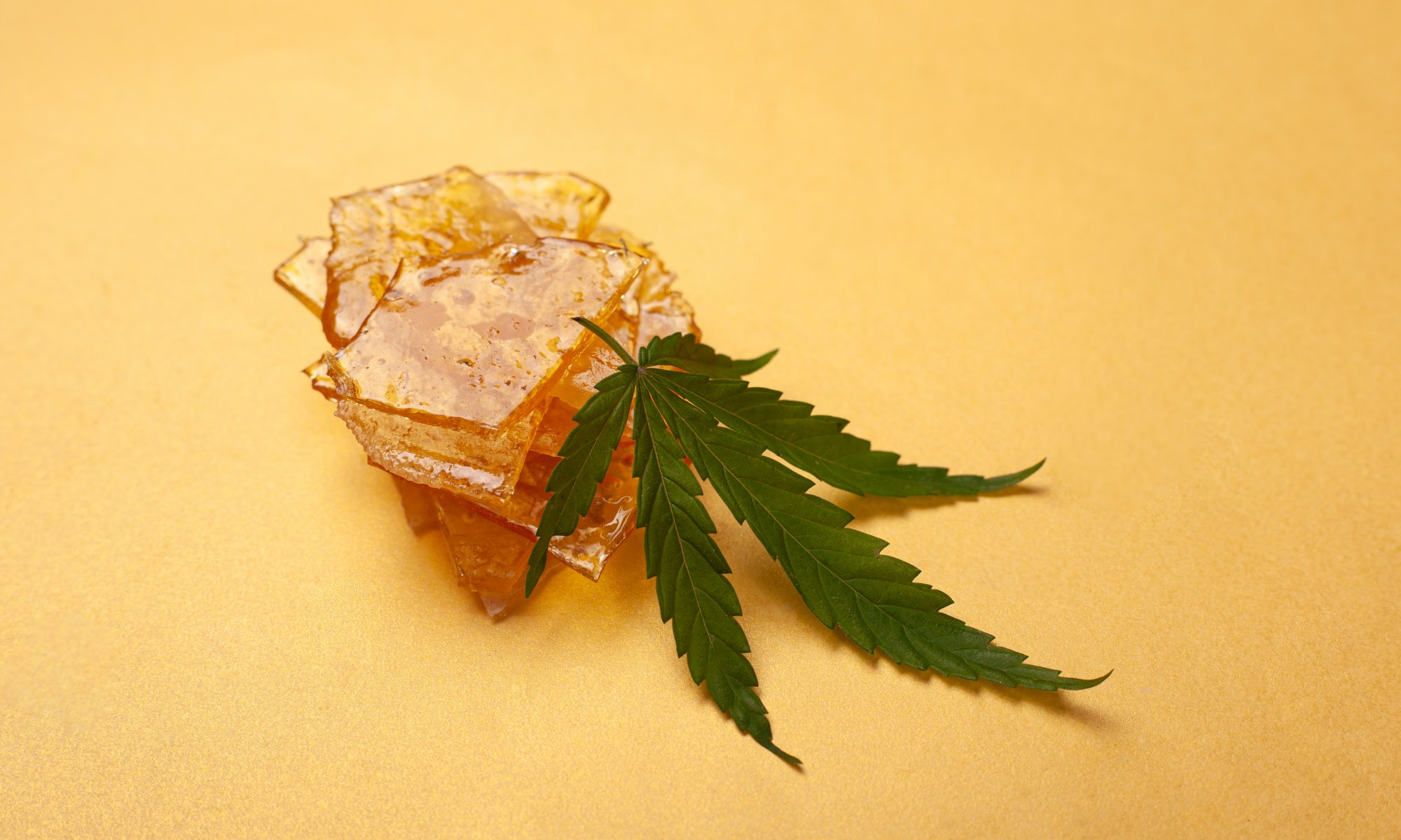 High,Thc,,Pieces,Of,Yellow,Cannabis,Wax,And,Green,Leaf,
