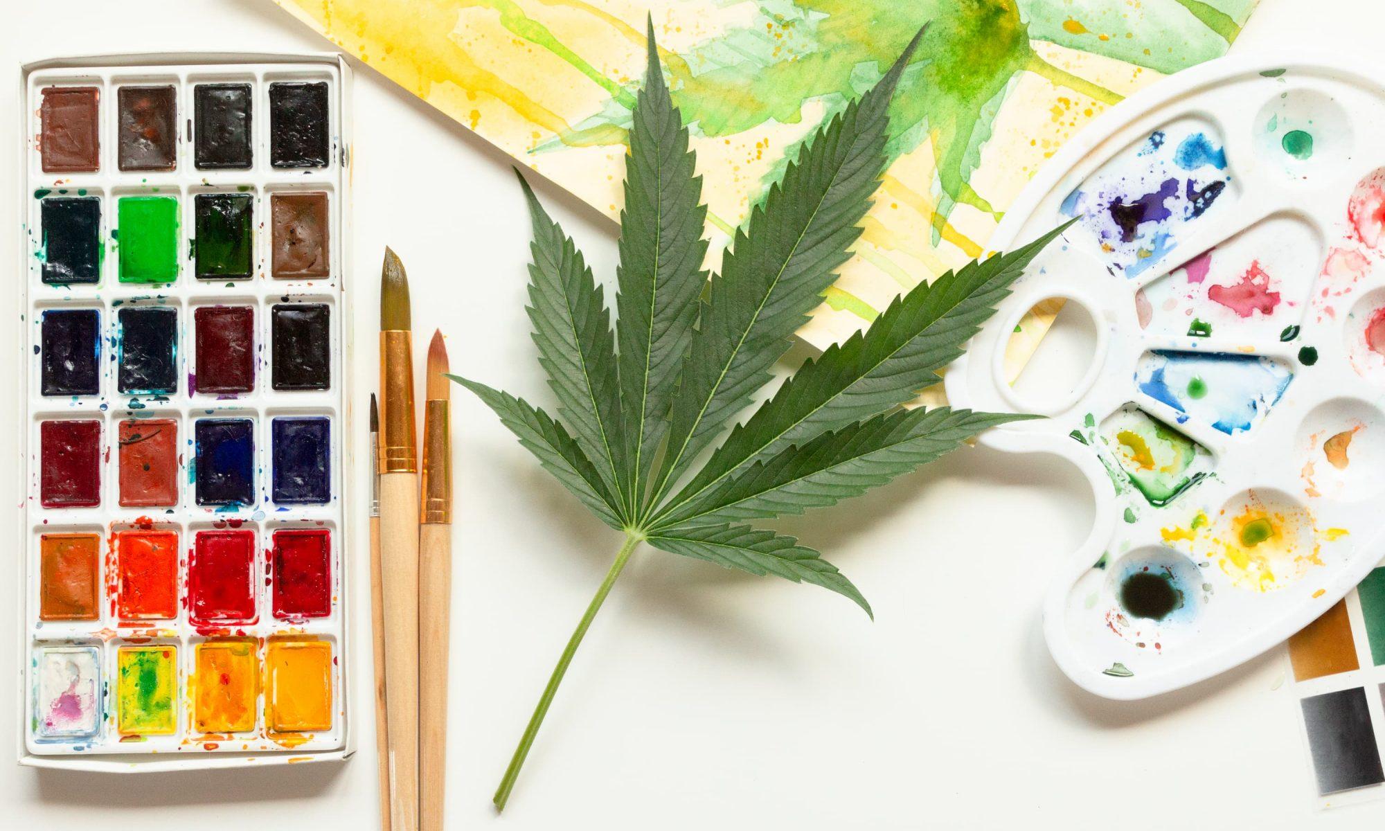 Painting art supplies next to a cannabis leaf